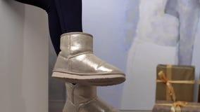 Τα πόδια της γυναίκας που ντύνονται στα χειμερινά υποδήματα, γυναίκα ταλαντεύονται το πόδι της, θερμή ντυμένη γυναίκα, χειμερινά  απόθεμα βίντεο