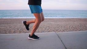 Τα πόδια του ισχυρού ατόμου στην πορεία κοντά στην ακροθαλασσιά στο χρόνο βραδιού, πλάγια όψη φιλμ μικρού μήκους
