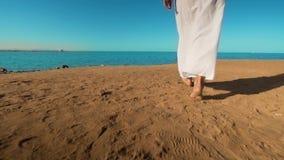 Τα πόδια του καυκάσιου κοριτσιού που φορούν το λευκό μακροχρόνιο ντύνουν την ξυπόλυτη άμμο περπατήματος στην παραλία θάλασσας φιλμ μικρού μήκους