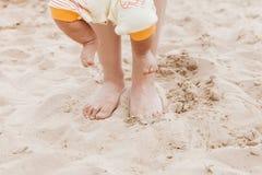 Τα πόδια του mom και του μωρού περπατούν κατά μήκος της άμμου το καλοκαίρι ηλιόλουστο Στοκ φωτογραφία με δικαίωμα ελεύθερης χρήσης