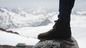 Τα πόδια τυχοδιωκτών στην μπότα δέρματος βαδίζουν βαριά στην πέτρα στη χιονώδη φυσική άποψη βουνών φιλμ μικρού μήκους