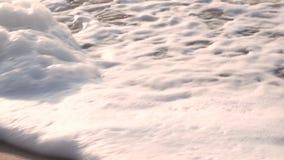 Τα πόδια των γυναικών αφήνουν τα σημάδια στην υγρή άμμο, και τα πλυσίματα κυμάτων μακριά με τον αφρό Θερινή θάλασσα απόθεμα βίντεο