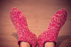 Τα πόδια ατόμων στο κόκκινο μαλλί κτυπούν βίαια το αρσενικό έπλεξαν το χειμώνα ενδυμάτων Στοκ Εικόνα