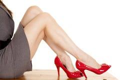 Τα πόδια γυναικών κάθονται τα γκρίζα κόκκινα τακούνια φορεμάτων στοκ φωτογραφία με δικαίωμα ελεύθερης χρήσης