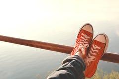Τα πόδια κόκκινων πάνινων παπουτσιών ένα κορίτσι στη φύση και χαλαρώνουν το χρόνο Στοκ Εικόνες