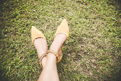 Τα πόδια με τη μόδα υψηλή βάζουν τακούνια στα παπούτσια κίτρινα στην πράσινη χλόη με το διάστημα αντιγράφων Εκλεκτής ποιότητας τό Στοκ Εικόνες