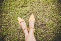 Τα πόδια με τη μόδα υψηλή βάζουν τακούνια στα παπούτσια κίτρινα στην πράσινη χλόη με το διάστημα αντιγράφων Εκλεκτής ποιότητας τό Στοκ φωτογραφίες με δικαίωμα ελεύθερης χρήσης