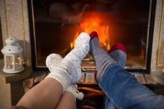 Τα πόδια στις μάλλινες κάλτσες τέντωσαν έξω τη θερμότητα επάνω κοντά στην εστία στοκ εικόνες