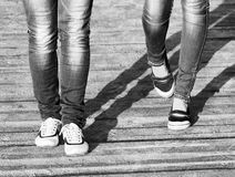 Τα πόδια δύο το κοριτσιών στα τζιν και τα άνετα παπούτσια ενώ περπάτημα/η γραπτή φωτογραφία Στοκ εικόνες με δικαίωμα ελεύθερης χρήσης