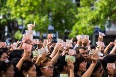 Τα πλήθη των θρηνητών κρατούν ότι τα ταϊλανδικά μετρητά για παρουσιάζουν εικόνα του βασιλιά Bhumibol κατά τη διάρκεια της τελετής Στοκ Εικόνα