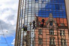 Τα πλυντήρια πλένουν τα παράθυρα του σύγχρονου ουρανοξύστη Στοκ Εικόνες