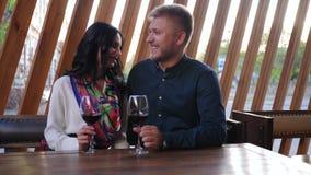 Τα ραντεβού, οι όμορφοι άνδρες και η γυναίκα με τα ποτήρια στα χέρια πίνουν το κρασί στον πίνακα στον καφέ απόθεμα βίντεο