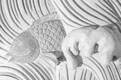 Τα ριγωτά ψάρια υποβάθρου κολυμπούν στη γλυπτική στο βράχο υπέροχα Στοκ εικόνα με δικαίωμα ελεύθερης χρήσης