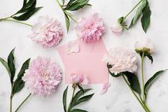 Τα ροζ peony λουλούδια, η κάρτα φακέλων και εγγράφου στην άσπρη άποψη επιτραπέζιων κορυφών πετρών στο επίπεδο βάζουν το ύφος Στοκ φωτογραφία με δικαίωμα ελεύθερης χρήσης