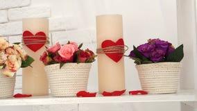 Τα ρομαντικά κεριά μήκους σε πόδηα ημέρας βαλεντίνων ` s με τις καρδιές και την κατάπληξη ανθίζουν στα δοχεία απόθεμα βίντεο