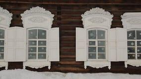 Τα ρωσικά χαρασμένα ξύλινα πλαίσια ωραιοποιούν το εξωτερικό του εφοδιασμένου με ξύλα σπιτιού απόθεμα βίντεο