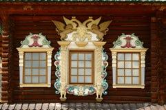 Τα ρωσικά χαρασμένα ξύλινα πλαίσια ωραιοποιούν το εξωτερικό του εφοδιασμένου με ξύλα σπιτιού Στοκ Φωτογραφία
