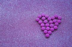 Τα ρόδινα χάπια που σχεδιάζονται στη μορφή μιας καρδιάς ακτινοβολούν επάνω ρόδινο υπόβαθρο στοκ φωτογραφίες