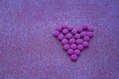 Τα ρόδινα χάπια που σχεδιάζονται στη μορφή μιας καρδιάς ακτινοβολούν επάνω ρόδινο υπόβαθρο στοκ εικόνες με δικαίωμα ελεύθερης χρήσης