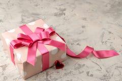 Τα ρόδινες κιβώτια και οι καρδιές δώρων κλείνουν επάνω σε ένα ελαφρύ συγκεκριμένο υπόβαθρο βαλεντίνος ημέρας s Διάστημα για το κε στοκ φωτογραφία με δικαίωμα ελεύθερης χρήσης