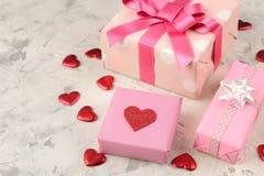 Τα ρόδινες κιβώτια και οι καρδιές δώρων κλείνουν επάνω σε ένα ελαφρύ συγκεκριμένο υπόβαθρο βαλεντίνος ημέρας s στοκ εικόνα με δικαίωμα ελεύθερης χρήσης