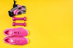 Τα ρόδινοι πάνινα παπούτσια, οι αλτήρες και τα αθλητικά γάντια βρίσκονται σε μια σειρά σε ένα κίτρινο υπόβαθρο στοκ φωτογραφία