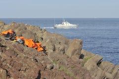 Τα σακάκια ζωής και οι βάρκες έφυγαν στην ελληνική δύσκολη παραλία και την ελληνική ακτοφυλακή στοκ εικόνες με δικαίωμα ελεύθερης χρήσης