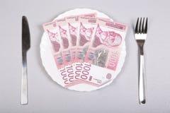 Τα σερβικά χρήματα Δηναρίων σε ένα άσπρο πιάτο με το δίκρανο και το μαχαίρι σε ένα γκρίζο υπόβαθρο, τοπ άποψη, επίπεδη βάζουν στοκ φωτογραφίες