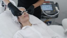 Τα σε αργή κίνηση χέρια του beautician στα γάντια βάζουν στα ειδικά προστατευτικά γυαλιά στα υπομονετικά μάτια απόθεμα βίντεο