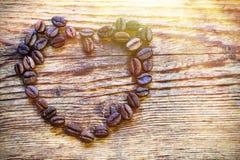 Τα σιτάρια καφέ είναι ευθυγραμμισμένα με μορφή μιας καρδιάς σε έναν ξύλινο κάπρο Στοκ φωτογραφία με δικαίωμα ελεύθερης χρήσης