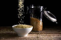Τα σιτάρια ρυζιού που περιέρχονται σε ένα λευκό κυλούν εκτός από ένα βάζο γυαλιού με ri Στοκ Φωτογραφία