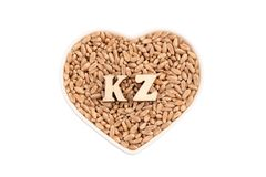 Τα σιτάρια σίτου βρίσκονται σε ένα άσπρο πιάτο με μορφή μιας καρδιάς KZ των ξύλινων επιστολών στο σιτάρι Απομόνωσε την έννοια της στοκ φωτογραφίες