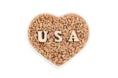 Τα σιτάρια σίτου βρίσκονται σε ένα καρδιά-διαμορφωμένο πιάτο ΗΠΑ από τις ξύλινες επιστολές στο σιτάρι r Η έννοια της εισαγωγής κα στοκ εικόνες