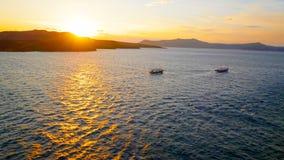 Τα σκάφη ταξιδεύουν τα ελληνικά νησιά στο ηλιοβασίλεμα, κοντά σε Santorini, στοκ φωτογραφίες