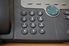 Τα σκοτεινά κουμπιά τηλεφωνικών πινάκων του τηλεφώνου γραμμών εδάφους με τους αριθμούς μαζί με μια ταχύτητα σχηματίζουν επάνω από στοκ φωτογραφία