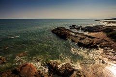 Τα σκοτεινά κυανά ωκεάνια κύματα πλένουν τη δύσκολη παραλία ενάντια στο μπλε ουρανό Στοκ Φωτογραφίες