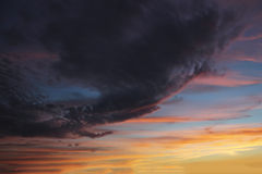 Τα σκοτεινά σύννεφα στον ουρανό στο ηλιοβασίλεμα μαίνονται Στοκ Φωτογραφία