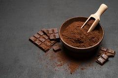 Τα σκοτεινά χοντρά κομμάτια και το κακάο σοκολάτας κονιοποιούν στην ξύλινη σέσουλα στο σκοτεινό συγκεκριμένο υπόβαθρο στοκ εικόνες