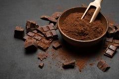 Τα σκοτεινά χοντρά κομμάτια και το κακάο σοκολάτας κονιοποιούν στην ξύλινη σέσουλα στο σκοτεινό συγκεκριμένο υπόβαθρο στοκ εικόνα