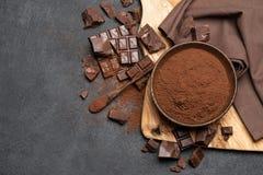 Τα σκοτεινά χοντρά κομμάτια και το κακάο σοκολάτας κονιοποιούν στο ξύλινο κύπελλο στο σκοτεινό συγκεκριμένο υπόβαθρο στοκ εικόνα με δικαίωμα ελεύθερης χρήσης