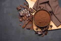 Τα σκοτεινά χοντρά κομμάτια και το κακάο σοκολάτας κονιοποιούν στο ξύλινο κύπελλο στο σκοτεινό συγκεκριμένο υπόβαθρο στοκ φωτογραφία