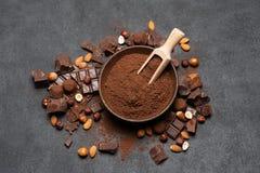 Τα σκοτεινά χοντρά κομμάτια, τα καρύδια και το κακάο σοκολάτας κονιοποιούν στο ξύλινο κύπελλο στο σκοτεινό συγκεκριμένο υπόβαθρο στοκ φωτογραφίες