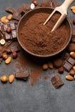 Τα σκοτεινά χοντρά κομμάτια, τα καρύδια και το κακάο σοκολάτας κονιοποιούν στο ξύλινο κύπελλο στο σκοτεινό συγκεκριμένο υπόβαθρο στοκ φωτογραφία με δικαίωμα ελεύθερης χρήσης