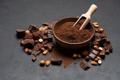 Τα σκοτεινά χοντρά κομμάτια, τα καρύδια και το κακάο σοκολάτας κονιοποιούν στο ξύλινο κύπελλο στο σκοτεινό συγκεκριμένο υπόβαθρο στοκ εικόνες