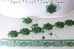 Τα σκουλαρίκια και το βραχιόλι χειροποίητα κρεμούν στη στάση Ραπτική στο σπίτι Κοσμήματα χαντρών Πράσινο χρώμα Σε μια άσπρη ανασκ στοκ φωτογραφία με δικαίωμα ελεύθερης χρήσης