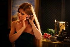 Τα σκουλαρίκια διαμαντιών γυναικών βάζουν στο αυτί της Κιβώτιο κοσμημάτων στον πίνακα Στοκ Εικόνες