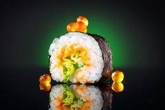 Τα σούσια κυλούν το μαύρο υπόβαθρο Τα σούσια κυλούν με τον τόνο, τα λαχανικά, τα πετώντας αυγοτάραχα ψαριών και την κινηματογράφη Στοκ εικόνες με δικαίωμα ελεύθερης χρήσης