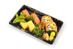 Τα σούσια σολομών και Καλιφόρνια Maki και το tamago Tamoko γεμίζουν με το μπιζέλι περιστεριών και τα πικάντικα τρόφιμα παράδοσης  Στοκ Εικόνα