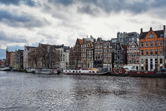 Τα σπίτια καναλιών κατά μήκος του ποταμού Amstel στο κέντρο πόλεων του Άμστερνταμ Στοκ Εικόνες