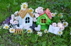 Τα σπίτια παιχνιδιών με τη σημείωση και το κείμενο σας αγαπούν, διακοσμήσεις, λουλούδια στη χλόη Στοκ φωτογραφίες με δικαίωμα ελεύθερης χρήσης